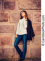 beautiful young fashionable girl standing against the stone...