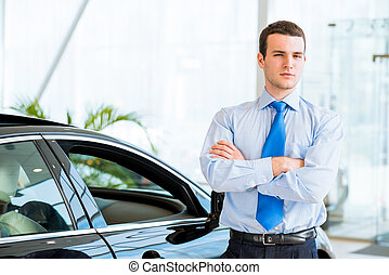 dealer stands near a new car in the showroom, folded his...