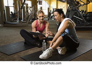 Woman with trainer at gym. - Prime adult Caucasian female...