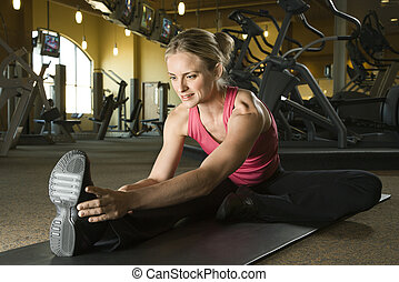 Woman stretching at gym - Prime adult Caucasian female...