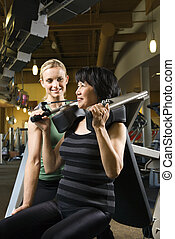 Woman at gym with trainer - Prime adult Caucasian female...