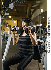 Woman using exercise machine - Mature Asian adult female...
