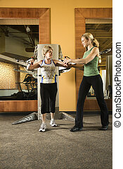 Woman helping woman excercise.