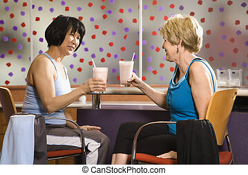 Women with health drinks. - Mature Asian and Caucasian adult...