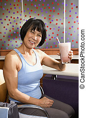 Woman with health shake - Mature Asian adult female sitting...