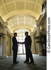 Two businessmen shaking hands. - Prime adult Asian and...