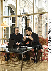 Two businessmen in hotel. - Prime adult Asian and Caucasian...
