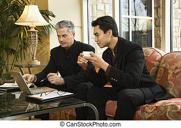 Two businessmen at hotel - Prime adult Asian and Caucasian...