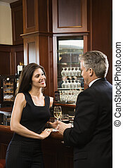 Man and woman at bar. - Prime adult Hispanic female and...