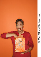 Woman with hand in gift bag. - African American mature adult...