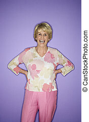 Woman standing and smiling. - Caucasian mature adult female...