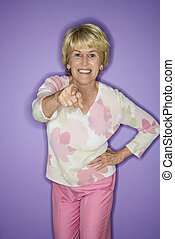 Woman pointing and smiling. - Caucasian mature adult female...