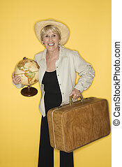 Woman holding suitcase and globe. - Caucasian mature adult...