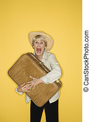 Woman grasping suitcase. - Caucasian mature adult female...