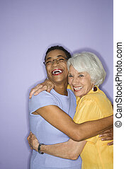 Women laughing - Caucasian and African American mature adult...