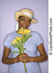 Woman with flowers. - African American mature adult female...