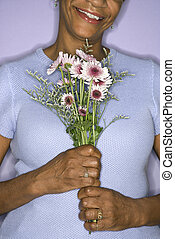 Woman holding flowers. - African American mature adult...