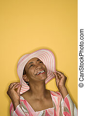 Woman holding her hat. - African American mature adult...