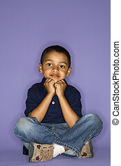 Portrait of cute boy. - African American male child sitting...