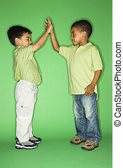 Boys giving high five. - Hispanic and African American male...