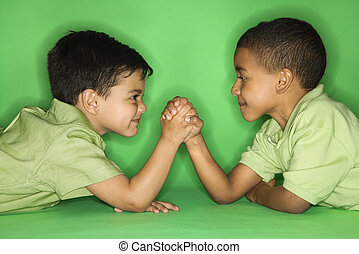 Boys arm wrestling. - Hispanic and African American male...