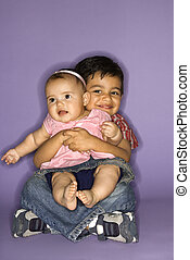 Boy holding baby girl. - Hispanic female baby and male child...