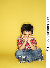 Boy sitting with head on hands. - Filipino male child...