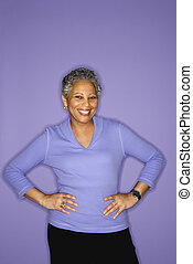 Woman standing and smiling. - African American mature adult...