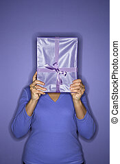 Woman hiding behind present. - African American mature adult...