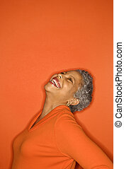 Woman with head back smiling. - African American mature...