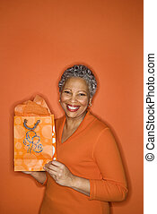 Woman holding gift bag. - African American mature adult...