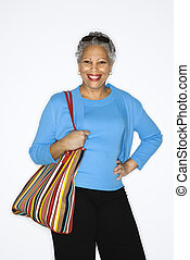 Woman holding big purse - African American mature adult...