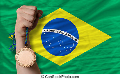 Bronze medal for sport and national flag of brazil - Holding...