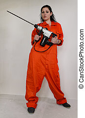 Woman in overalls holding an electric drill