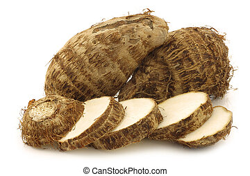 fresh taro roots and a cut one - two fresh taro roots and a...