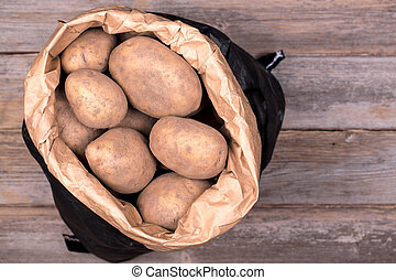Sack of potatoes - Unwashed potateos in a black and brown...