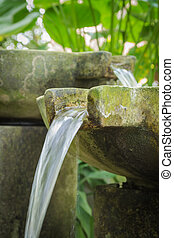 Flowing water from stone basin in the garden