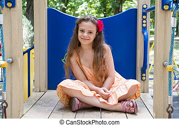 Little girl sitting on the playground