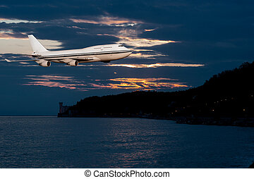 passenger airplane in the clouds at sunset or dawn. Tourist...
