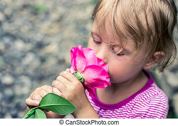 beautiful greeting child smelling a rose