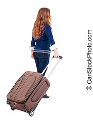 back view of walking woman with suitcase beautiful redhead...