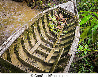 A erode wooden ship is covered by mud and moss