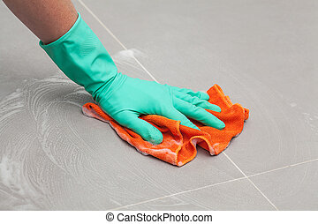 Floor cleaning rag - A man in a glove cleaning the floor...
