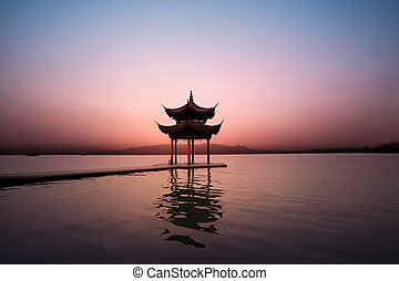 the west lake in hangzhou at dusk - pavilion at...