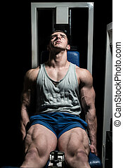 bodybuilder doing heavy weight exercise for legs on machine...