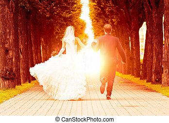 wedding sunset - bride and groom is jumping with joined...