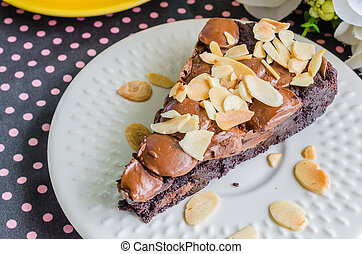 Brownie cake on white dish with almondchocolate chip