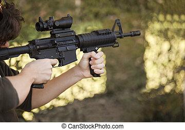 Adolescente, máquina, arma de fuego