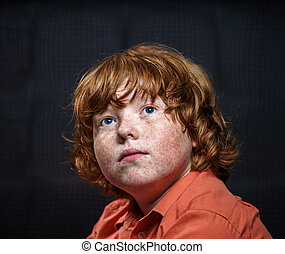 Freckled red-hair boy posing on dark background Emotions
