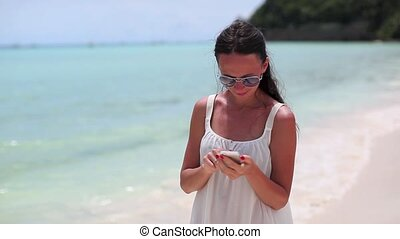 Young beautiful woman on the beach looking on her phone -...